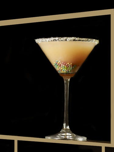 "<p>2 oz. vodka<br /> 2 oz. white peach puree <br /> 1 oz. ginger-infused simple syrup <br /> ½ oz. lemon juice<br /> Silver and pink sanding sugar (for rim) <br /> Silver sugar beads</p>  <p>To make the peach puree, peel a peach and put it in a blender for about 10-15 seconds. To make the ginger syrup, bring half a cup of water and half a cup of sugar to a boil in a small saucepan. Throw in some fresh chopped ginger. Reduce, and stir until the mixture thickens. Strain out the ginger and let the syrup cool to room temperature Now, in a mixing glass, combine the peach puree, the ginger syrup, the lemon juice and the vodka; shake. Strain into a martini glass rimmed with the sanding sugar. (If you can't find sanding sugar in the baking aisle of your supermarket, substitute a small candy, like Nerds, crushed into powder.) Drop the silver sugar beads in the bottom of the glass for more ""bling.""</p>"