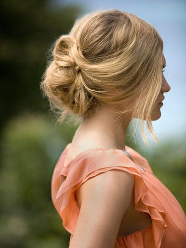 """You know how you twist your hair when you're bored on a lazy day? That's the key trick to this style, according to NYC stylist Leon Gorman, who created the looks seen here. Make a low side ponytail, leaving a few pieces loose around your face. Twist the length of your ponytail, and wrap it into a figure-eight shape — smoosh it up against your scalp, and tuck the ends into the loop. Insert a few hairpins or tiny barrettes to lock it all in place. Finish with a mist of lightweight hair spray that'll give you extra hold minus any stickiness. We like <a href=""""http://www.paulmitchell.com/Products/PaulMitchell/ExpressStyle/Pages/WorkedUp.aspx"""" target=""""_blank"""">Paul Mitchell Worked Up</a>, $14.95."""
