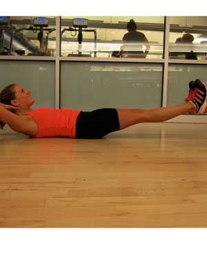 Start by lying down on your back, with your legs straight and spread wider than shoulder-width. Crunch up while clicking your heels together for a second. Move them back to their original starting position, and do 10 to 15 reps.