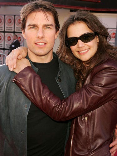 At the beginning of their relationship in 2005, Katie's smile is genuine. By looking straight ahead, Tom seems disconnected to her.