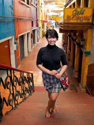 "<p>A trendy skull and rose print bag instantly amps up a mock-neck top and plaid skirt getup. Glenda Canizales, owner of Mua Cafe, a coffee shop, boutique, and performance space,located on Pasaje Gomez in Tijuana.</p> <p> </p> <p>Alicia Santistevan, photographer,<a href=""http://www.aliciasantistevan.com/"" target=""_blank""> AliciaSantistevan.com </a></p>"