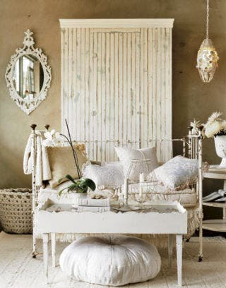 White daybed with pillows and table
