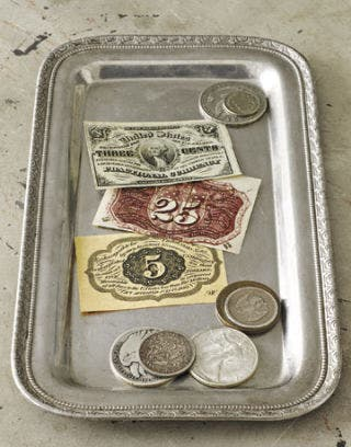 antique currency on a silver platter