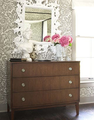 white mirror above brown dresser with white statue and flowers