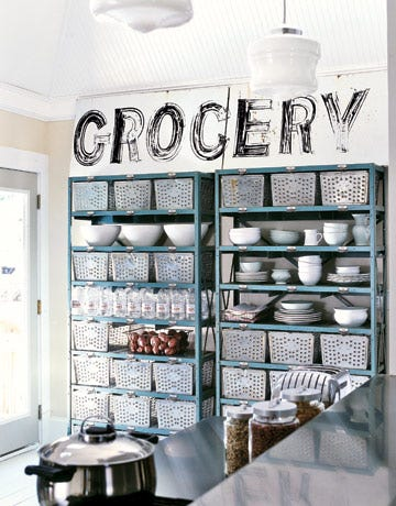 blue metal shelves hold bins dishes water and potatoes with a sign that says grocery above