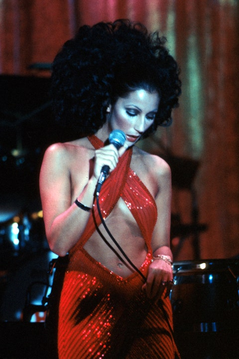 cher performing in 1972 in a red dress and curly hair