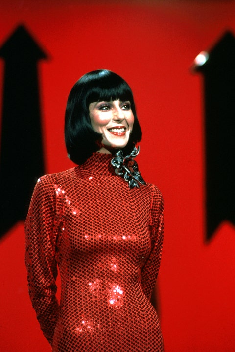 cher wearing a red sequin dress and a bob haircut