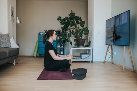 adult woman taking online yoga lessons during lockdown in isolation