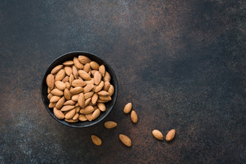 almonds in bowl on background