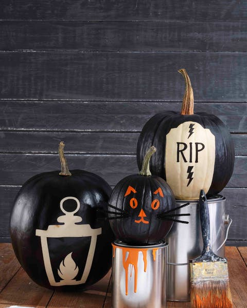 painted reverse image pumpkins of a lantern, cat face, and gravestone