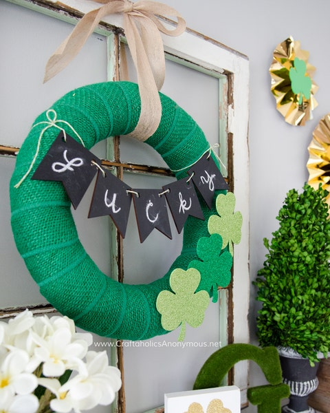 "green burlap wreath with three glitter foam shamrocks and a ""lucky"" banner tied across it it is hanging on a window frame which is sitting on a mantel"