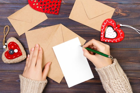 cropped hands of woman making valentine card on table