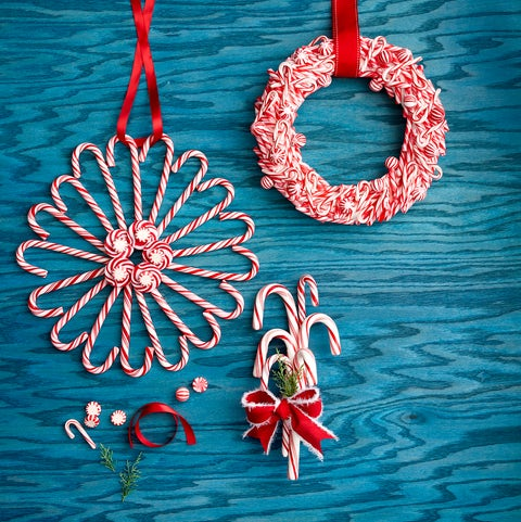 two wreaths made out of candy canes and one door swag made out of giant candy canes and tied with ribbon
