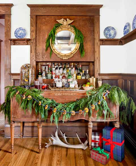 a dried citrus garland with plaid ribbon is layered on a swag of greenery that is draped on a bar