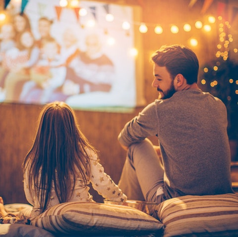 father and daughter sitting at backyard and looking movie at home improved theatre backyard is decorated with string lighs