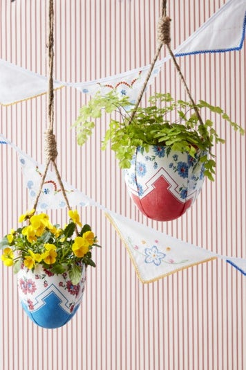 Hanging planters wrapped in scarves with flowers