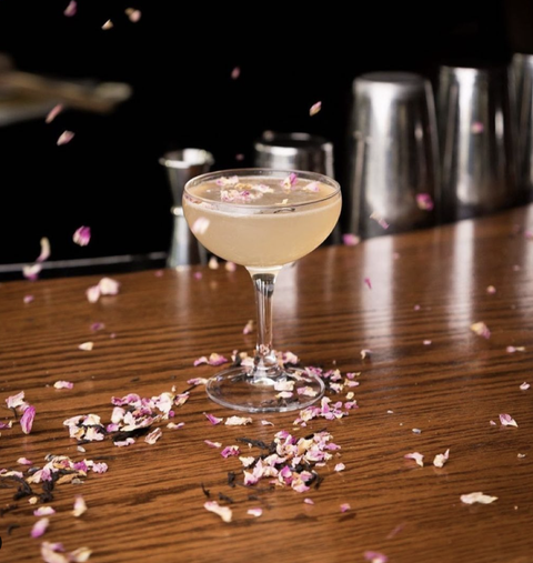 drink with flower petals falling around