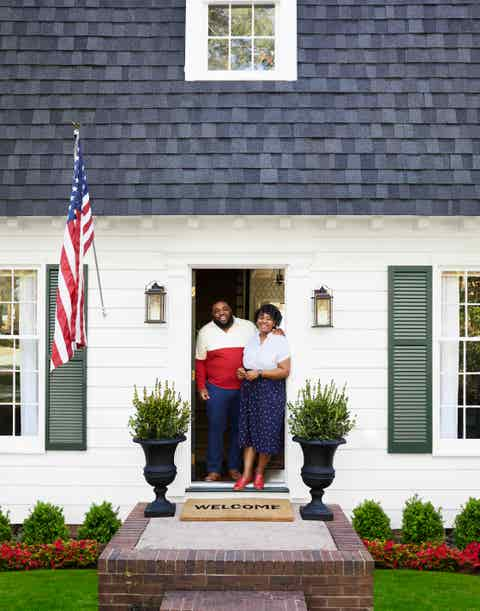 makeover takeover exterior with couple standing in doorway