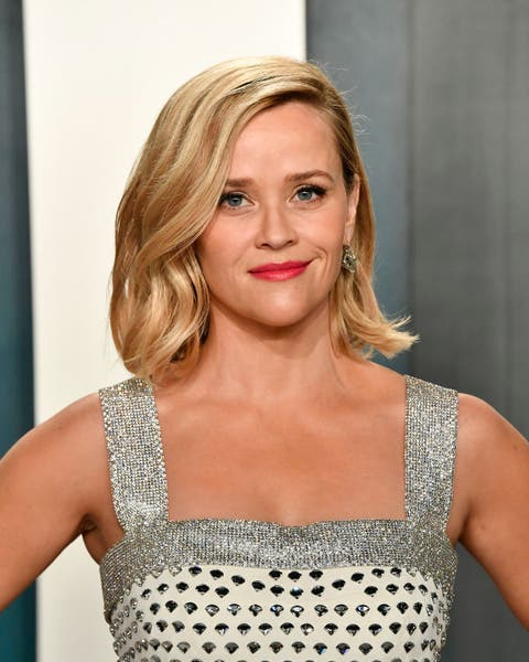 reese witherspoon wears a white and silver dress on the red carpet