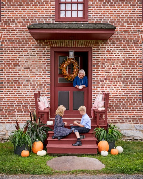 small porch with built in benches decorated with pillows and pumpkins