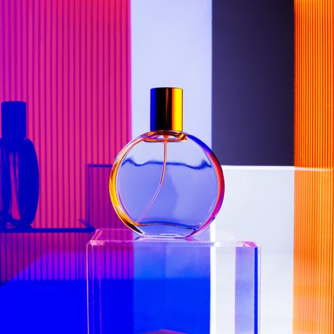 blue fragrance bottle on rainbow background