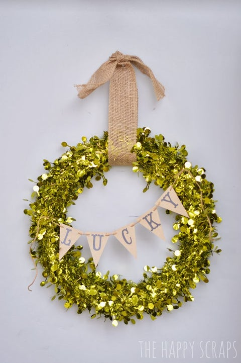 "gold glitter round wreath with a banner reading ""lucky"" across it"