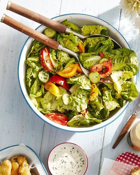 green salad with tomatoes, cucumber, and green goddess dressing