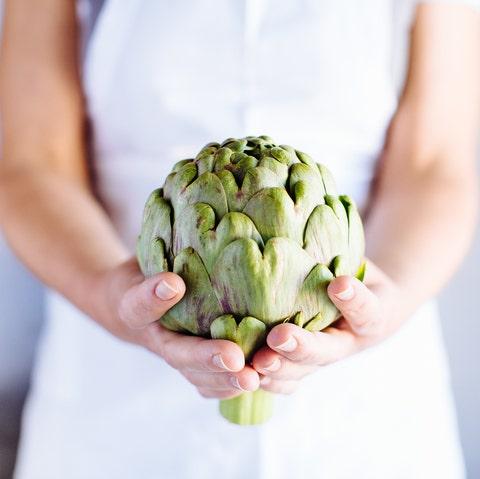 Traditional Italian food preparation, womans hands holding globe artichoke, Campania, Italy